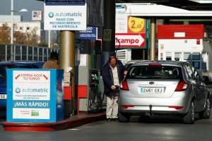 Un hombre se sirve carburante en una gasolinera.