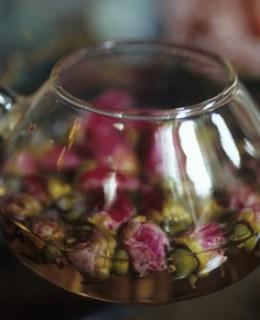 Une théière remplie de roses dans l'eau