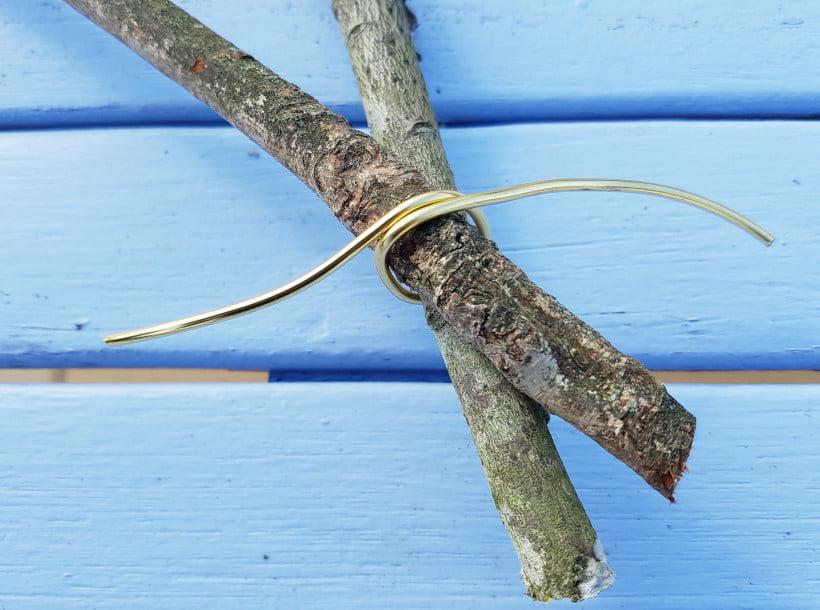 Fabrication d'une étoile de Noël avec des branches coupées au jardin - attache métallique dorée