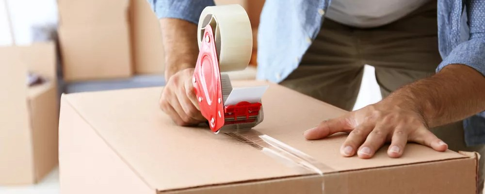 Man sealing moving box with packing tape
