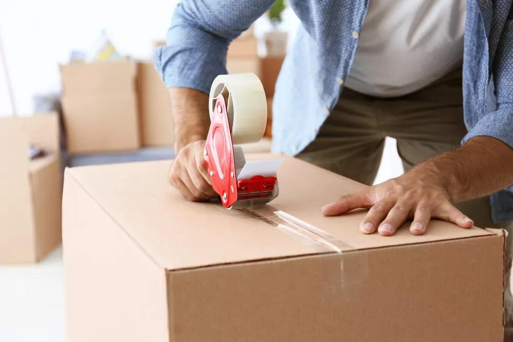 Man sealing moving box with packing tape