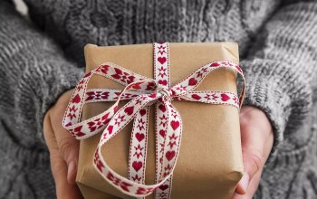 Hands holding brown box wrapped in red ribbon