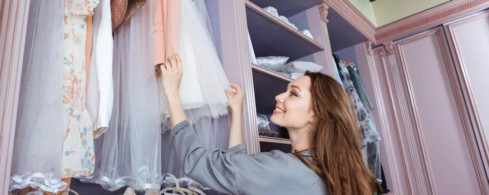 Young woman looking through wardrobe