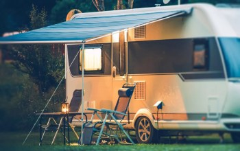 RV camper at night with chairs under canopy