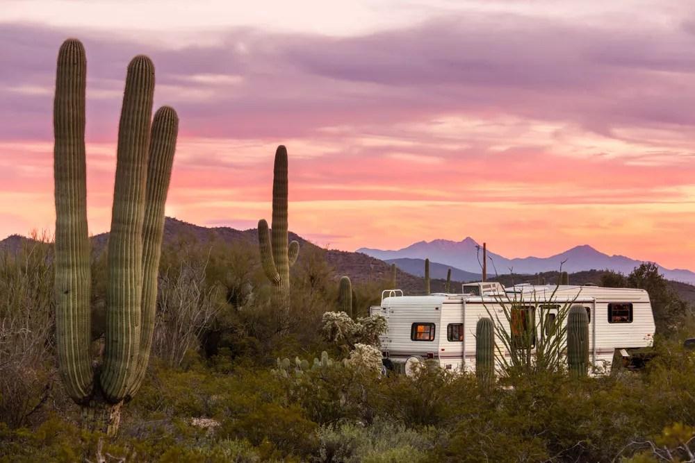 RV sitting in southwestern desert at sunset