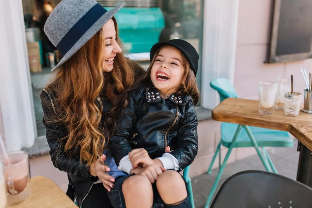 Young mother and daughter in the big city at a cafe