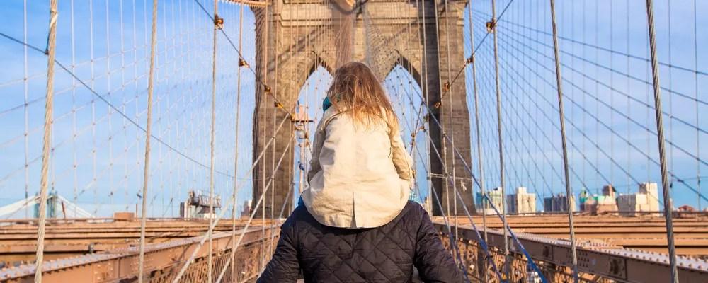Dad carrying daughter on shoulders on Brooklyn Bridge