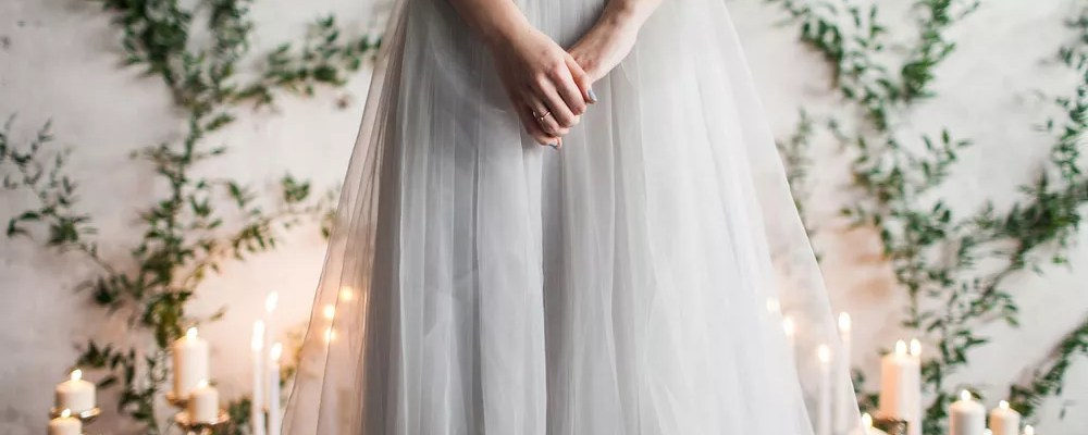 Bride with hands clasped standing at altar