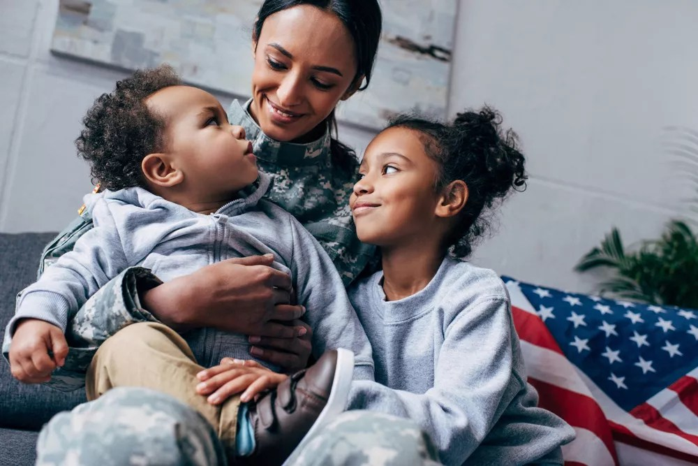 Military woman and her two kids hugging.