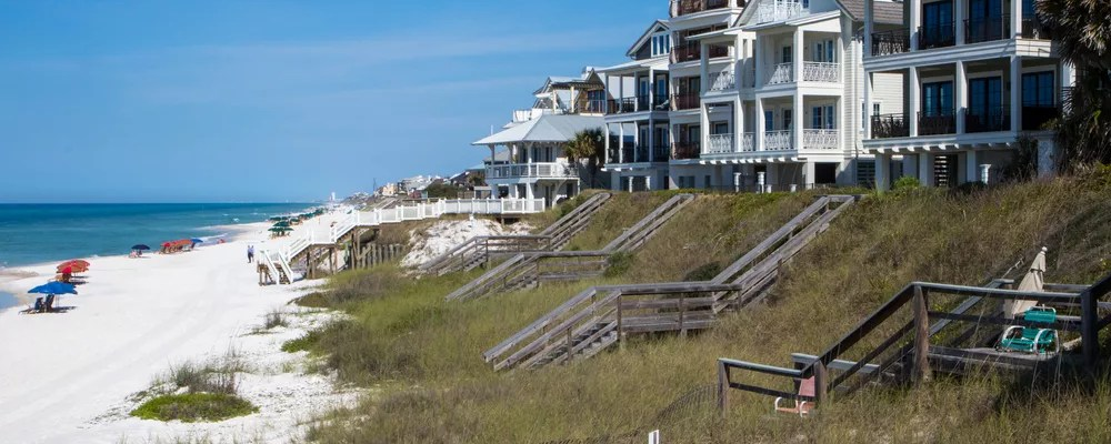 Homes on grassy hill by the beach.