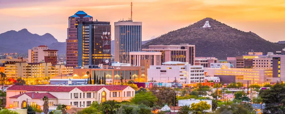 Skyline of tall buildings and a mountain during sunset in Tucson