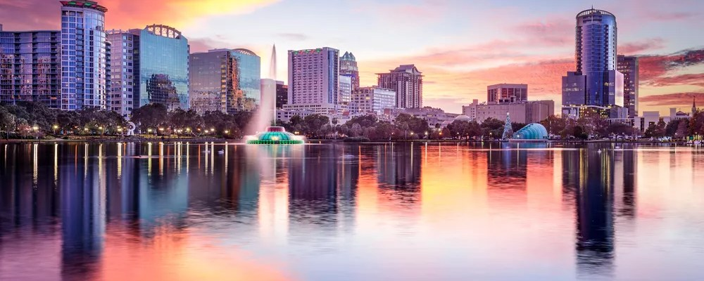 Skyline of buildings in Downtown Orlando next to water.