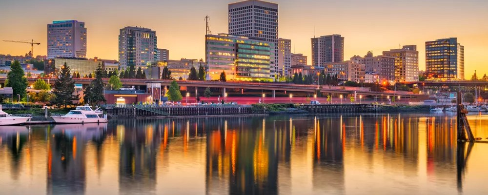 Tall buildings lit up next water at sunset in Downtown Tacoma