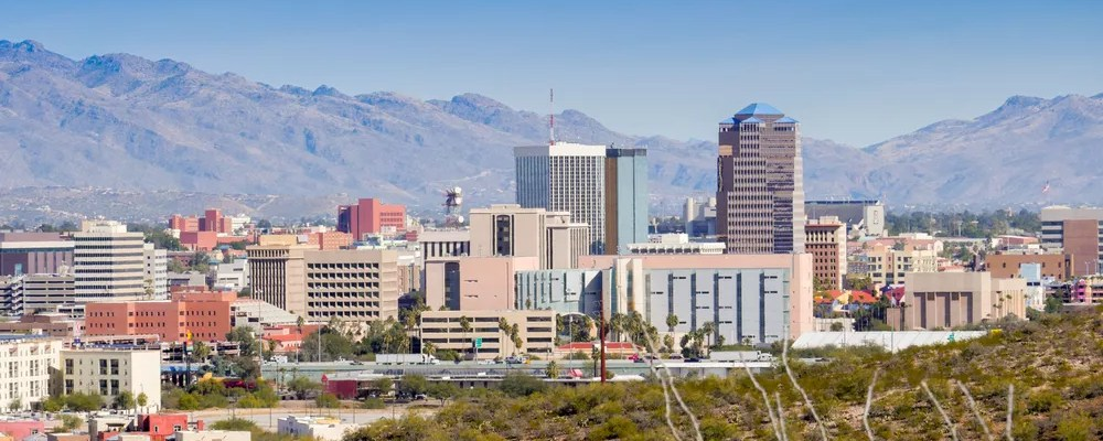 Skyline of tall buildings surrounded by mountains in Tucson.