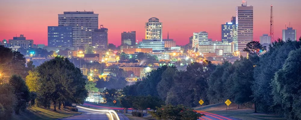 Skyline of tall buildings with lights on at night time in Columbia, SC.