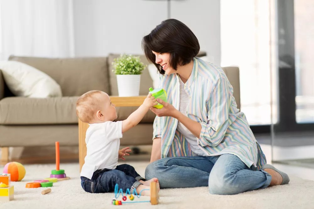 Mom playing with baby in living room