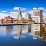Skyline of Downtown Providence RI from the Providence river with blue sky and clouds