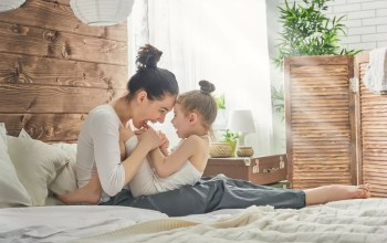 Mom and young daughter playing on bed