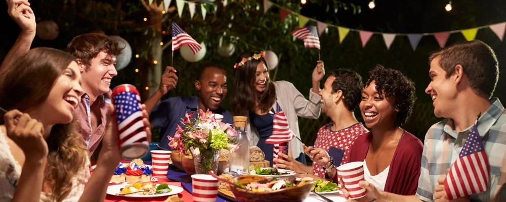 Large Group of People Sitting Around a Table at a Fourth of July Party