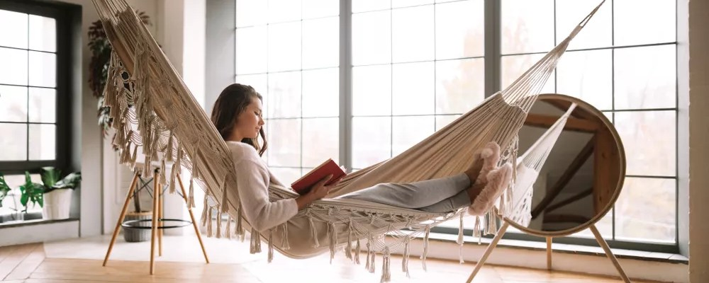 Woman Reading a Book in a Hammock in Her Home