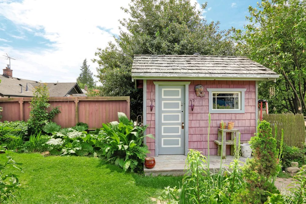Pink She Shed in a Back Yard with Nice Landscaping Nearby