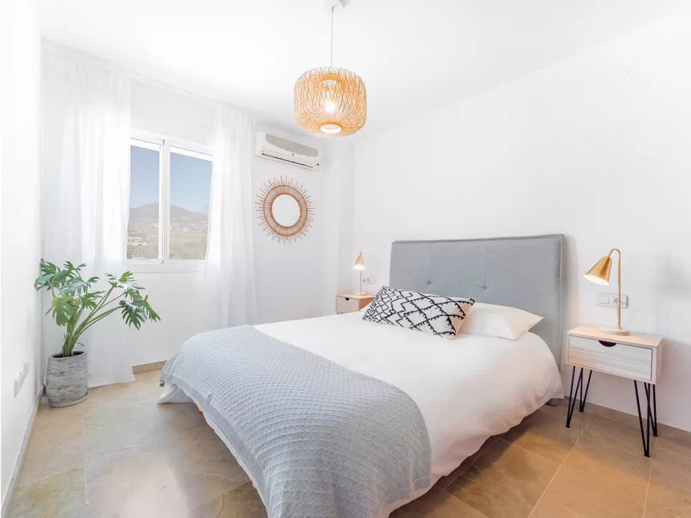 Clean Bedroom with White Walls and White and Blue Bedspread