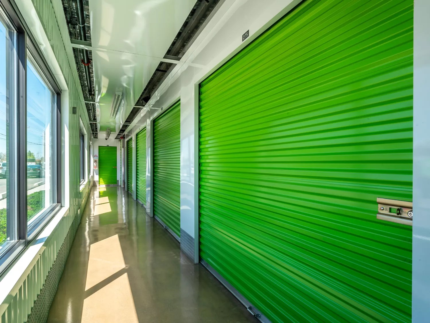 View down a hallway of an Extra Space Storage facility; hallways is clean, well-lit, and has bright green garage-like doors