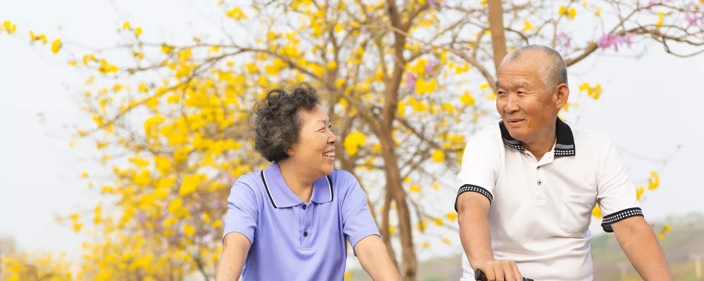 Older Asian Man and Woman Riding Bikes in Fall
