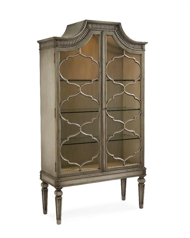 The Freya display cabinet on stand, finished in Trentino grey, has a swept top with carving and fluting above the two barred doors. There is one touch-sen