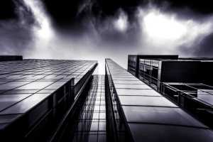 A black and white photo of a city building shot from below, up close