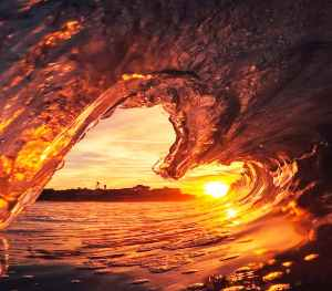 Inside the curl of an ocean wave at sunset