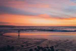 A surfer walks along the beach at sunset