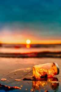 A jar full of LED string lights lies on its side in the sand on a beach
