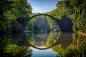 A stone bridge arches over a still lake