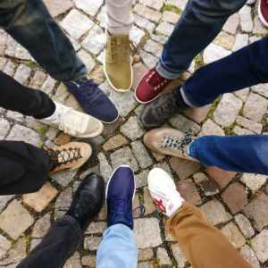 Several people place their feet together in a circle