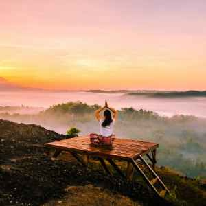 A woman sits on a wooden platform overlooking a misty valley