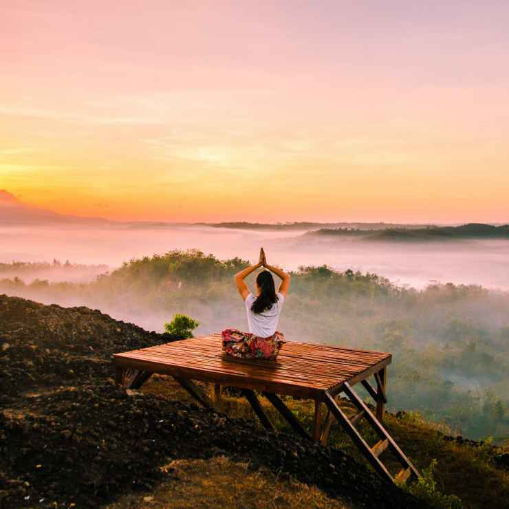 A woman doing yoga while looking over a misty valley