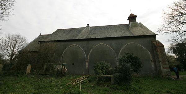 Side view of the church. The arches are all that remains of the 12th century priory.