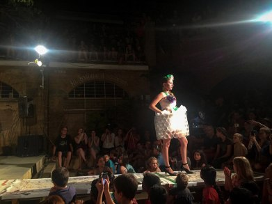 A saran and plastic cup cocktail dress with flower accents made from plastic bottle bottoms.