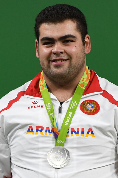 Armenia's silver medallist Gor Minasyan poses on the podium of the Men's +105kg weightlifting competition at the Rio 2016 Olympic Games in Rio de Janeiro on August 16, 2016. / AFP / GOH Chai Hin (Photo credit should read GOH CHAI HIN/AFP/Getty Images)