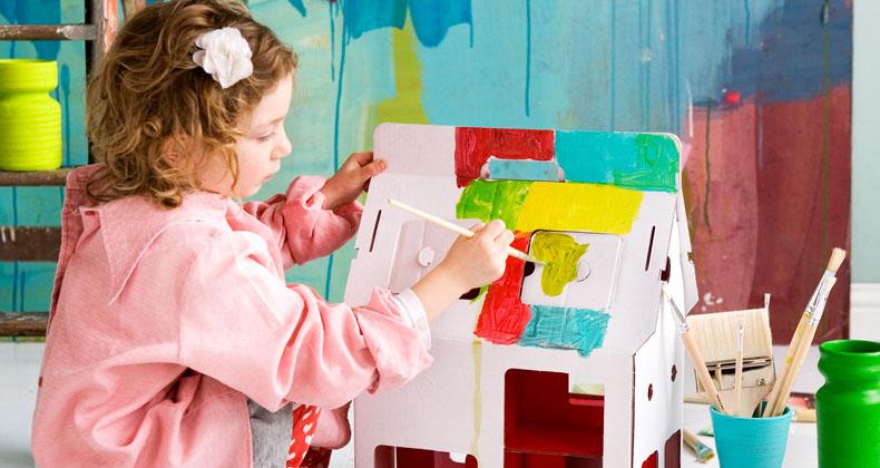 Niña pintando casita de muñecas de cartón