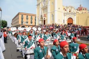 Familias enteras y xalapeños de todas las edades participan o presencian los desfiles del 5 de mayo, tal y como se aprecia en esta imagen de este año con la catedral como telón de fondo.