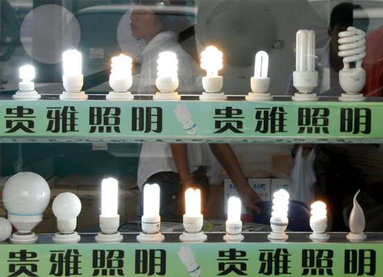 Una vendedora camina junto a un escaparate lleno de bombillas situado en un mercado de Pekín (China).