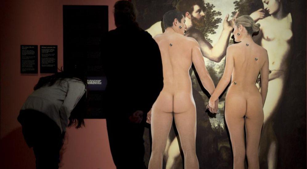 Una pareja desnuda de espaldas en una exposición
