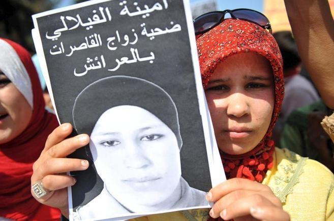 La hermana de Amina Al Filali, sostiene un cartel con la fotografía...