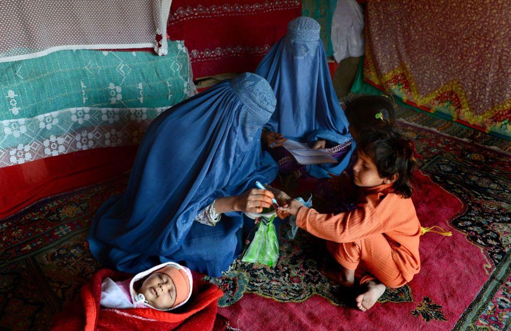 Unas trabajadoras sanitarias afganas vestidas con burkas marcan el dedo de un niño después de administrar la poliomielitis.