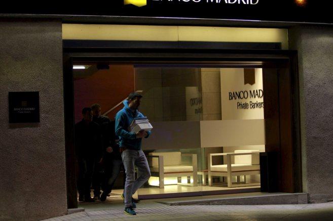 Un agente de la Policía Nacional abandona la sede de Banco Madrid,...