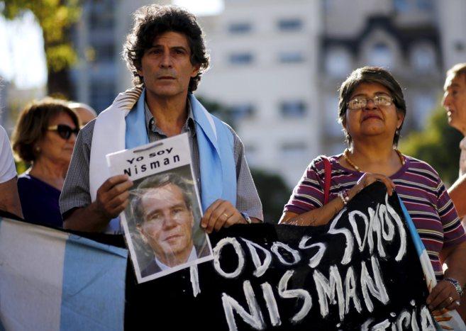 Dos manifestantes en Buenos Aires  sostienen una pancarta de Nisman,...