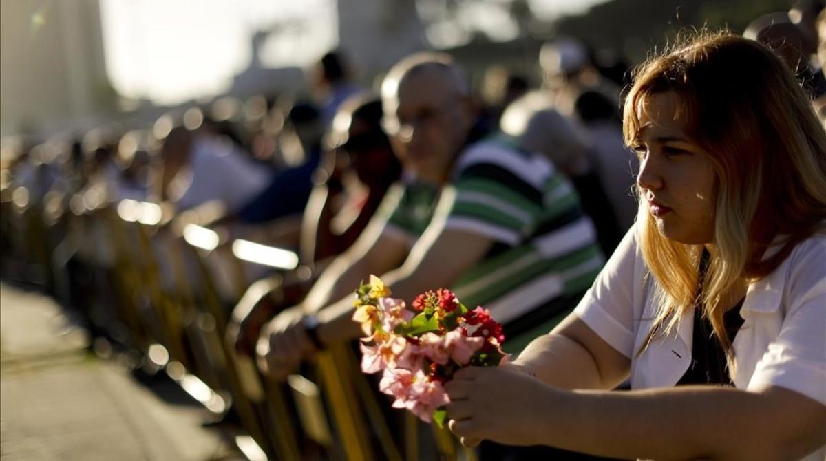 https://i0.wp.com/estaticos.elperiodico.com/resources/jpg/0/7/amanda-reyes-rodriguez-sostiene-unas-flores-mientras-espera-cola-para-despedirse-fidel-plaza-revolucion-este-martes-1480452989670.jpg