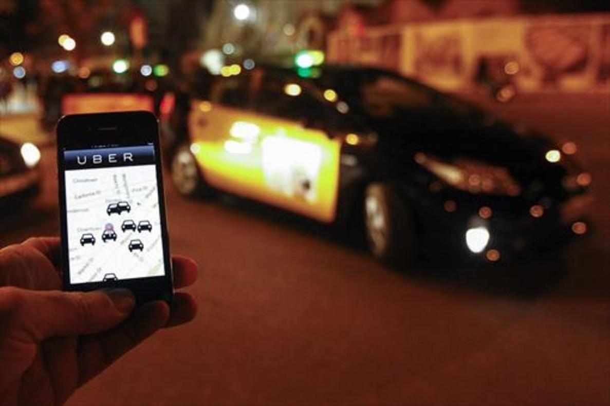 Un usuario consulta la aplicación de Uber junto a la Sagrada Família, en diciembre del 2014.